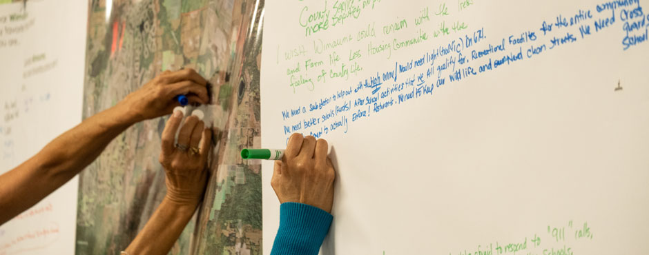people writing comments on posters at the March 2020 Wimauma Open House
