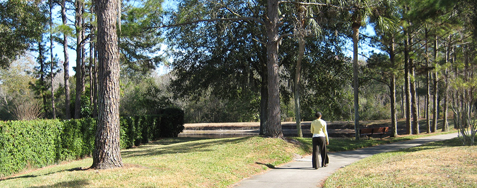 woman walking on wooded, manicured path