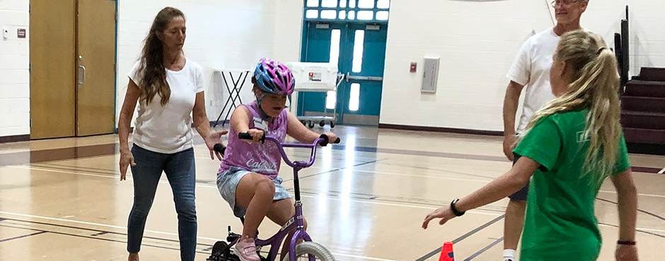 disabled child being taught how to ride a bike