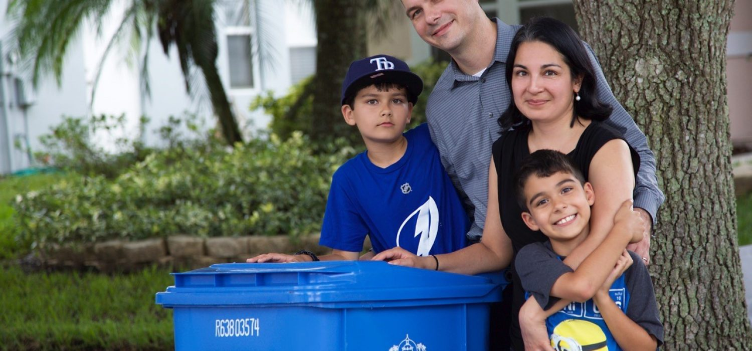 Family posing with waste bins